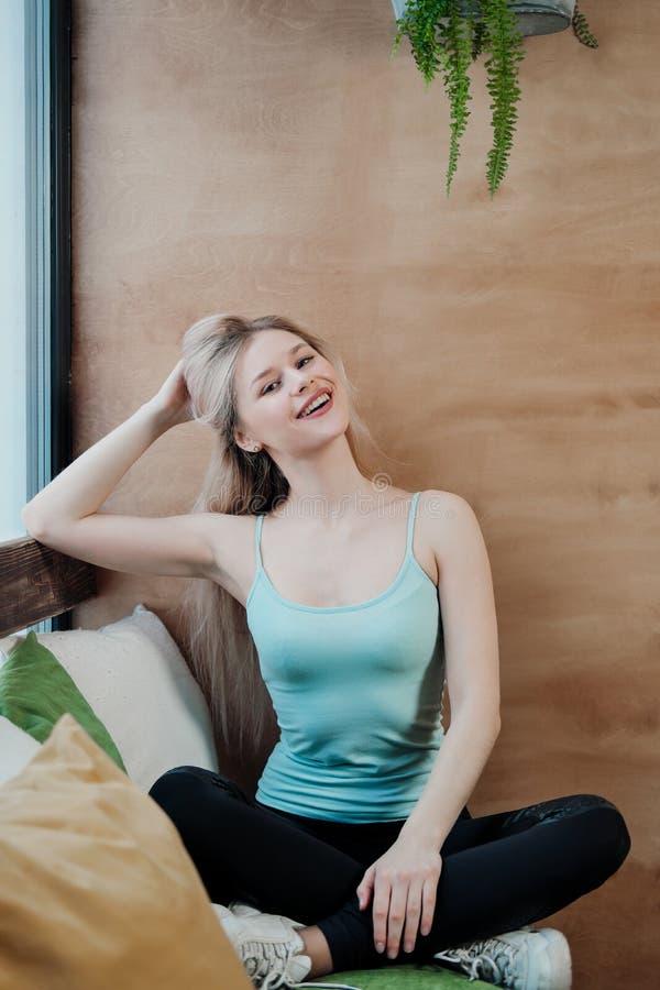 Jeune belle femme sportive blonde en tenue de sport assise devant la fenêtre d'un café sur fond de bois images stock