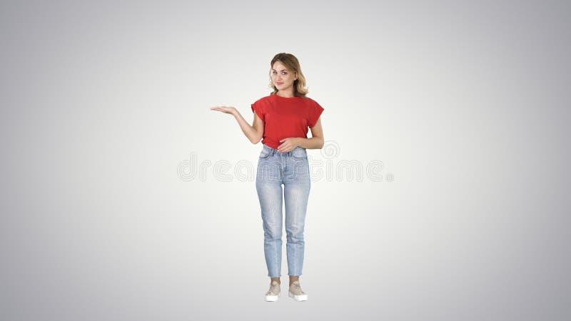 Jeune belle femme stupéfaite et souriante à la caméra tout en présentant quelque chose avec la main sur le fond de gradient photographie stock libre de droits