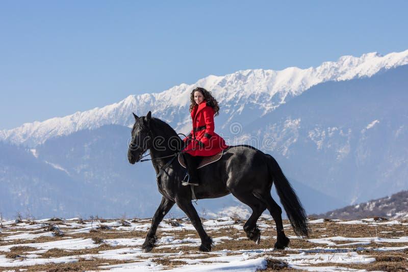 Jeune belle femme sur le cheval noir dans la monte en montagnes de la Transylvanie images stock