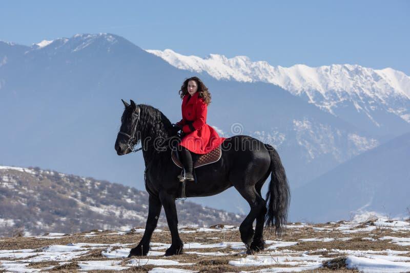 Jeune belle femme sur le cheval noir dans la monte en montagnes de la Transylvanie photo libre de droits