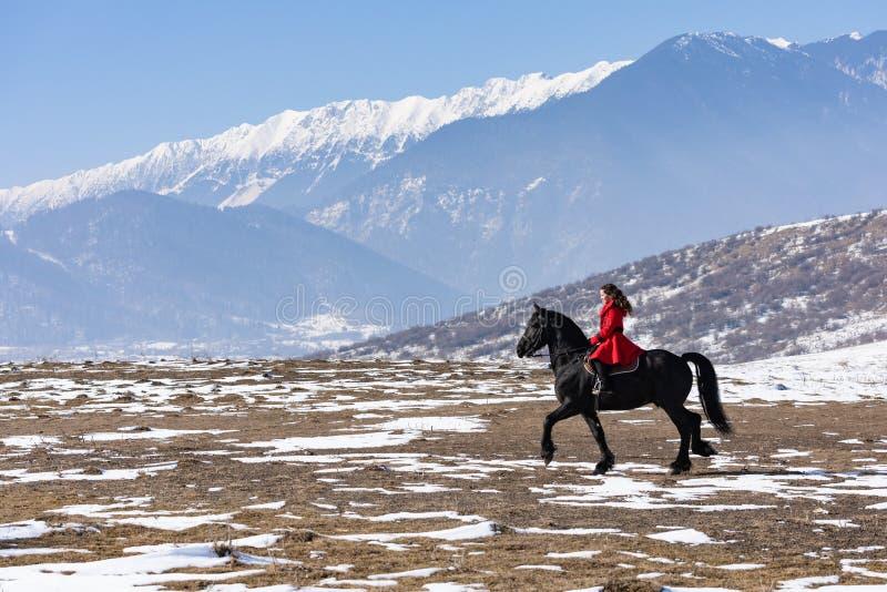 Jeune belle femme sur le cheval noir dans la monte en montagnes de la Transylvanie photos libres de droits