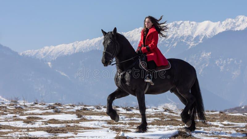Jeune belle femme sur le cheval noir dans la monte en montagnes de la Transylvanie images libres de droits