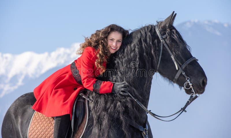 Jeune belle femme sur le cheval noir dans la monte en montagnes de la Transylvanie photo stock