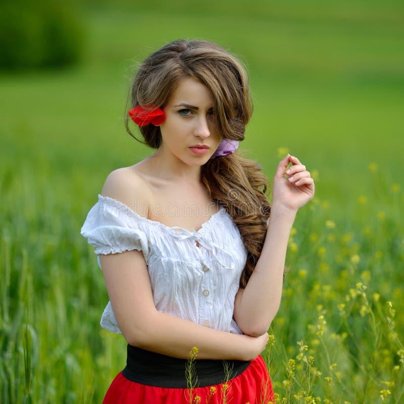 Jeune belle femme sur le gisement de céréale avec des pavots photos libres de droits