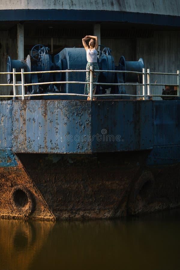 Jeune belle femme sur un bateau géant abandonné en métal image libre de droits