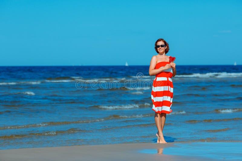 Jeune belle femme tenant le coeur de sucrerie et appréciant des vacances de plage d'été photos libres de droits