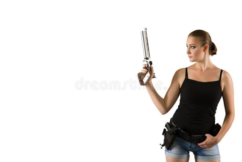 Jeune belle femme tenant une arme à feu de sport sur le fond blanc image libre de droits