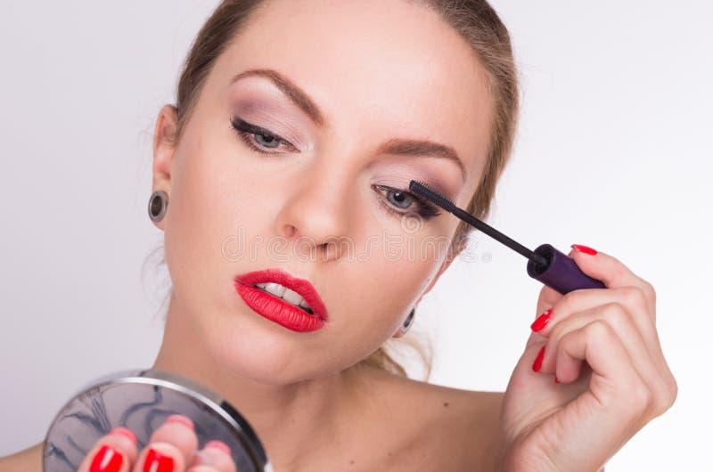 Jeune belle femme tenant une brosse et colorant ses cils images libres de droits