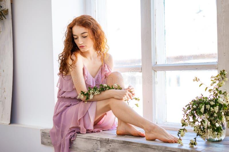 Jeune belle femme triste par la fenêtre, beaux cheveux rouges images stock