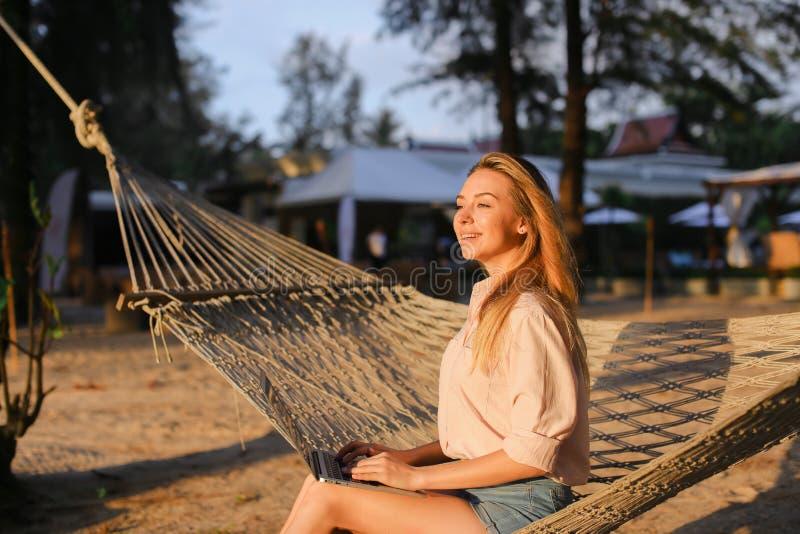 Jeune belle fille à l'aide de l'ordinateur portable et se reposant sur le sable dans l'hamac en osier photo libre de droits