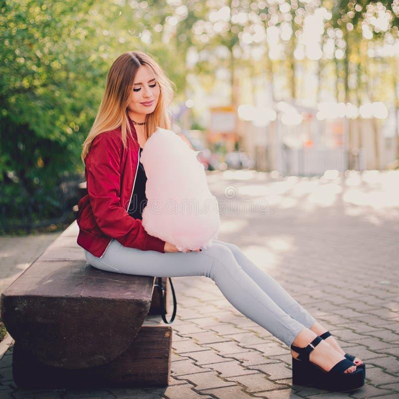 Jeune belle fille élégante s'asseyant sur le banc en parc avec la sucrerie de coton photos stock
