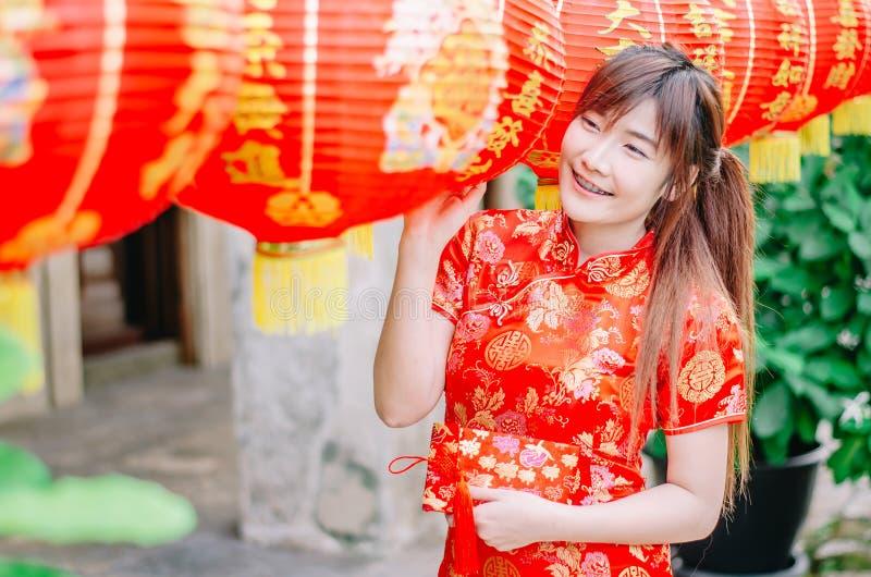 Jeune belle fille asiatique dans le support rouge traditionnel chinois de sourire de robe près de la lampe de porcelaine, par nou photos libres de droits