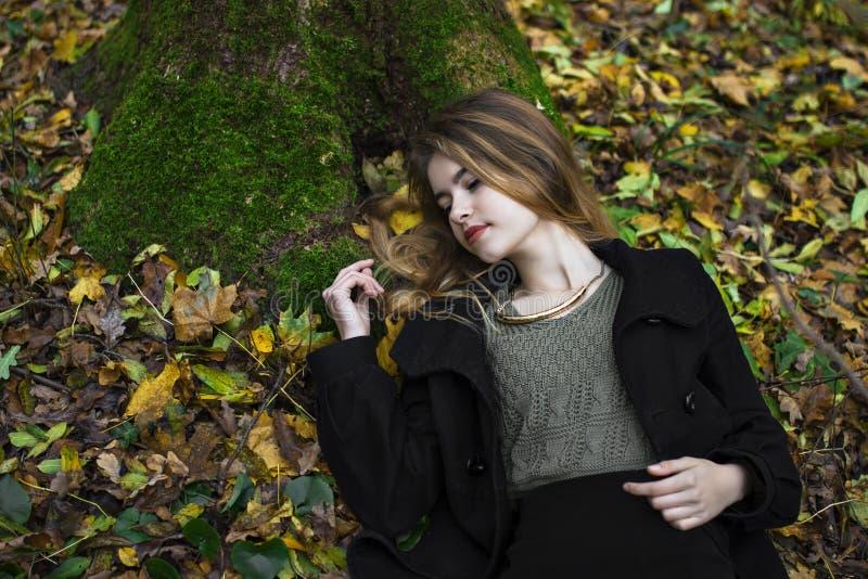 Jeune belle fille au milieu des feuilles d'automne à l'arrière-plan photographie stock