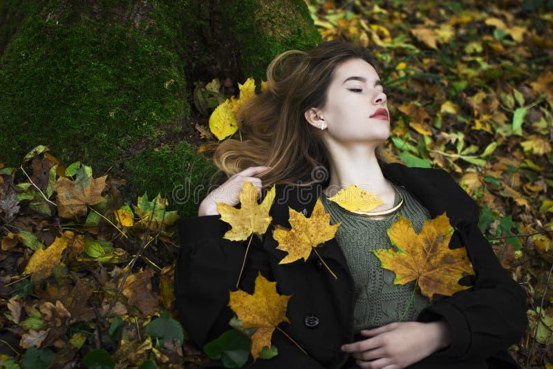 Jeune belle fille au milieu des feuilles d'automne à l'arrière-plan photo stock