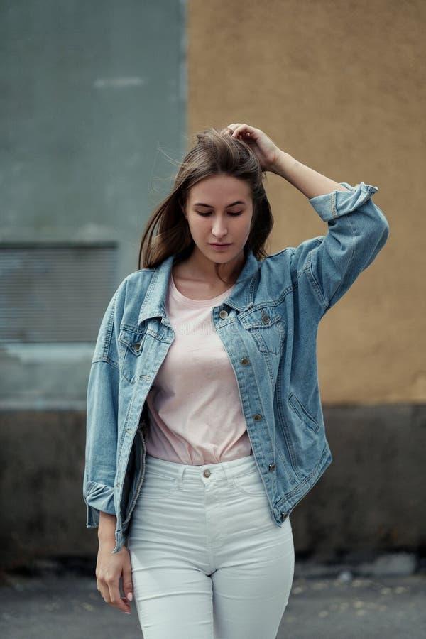 Jeune belle fille avec de longs cheveux dans une veste de T-shirt et de denim sur le fond du mur en béton de cru image stock