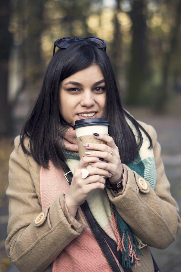 Jeune belle fille avec du café dans une tasse de papier photos libres de droits