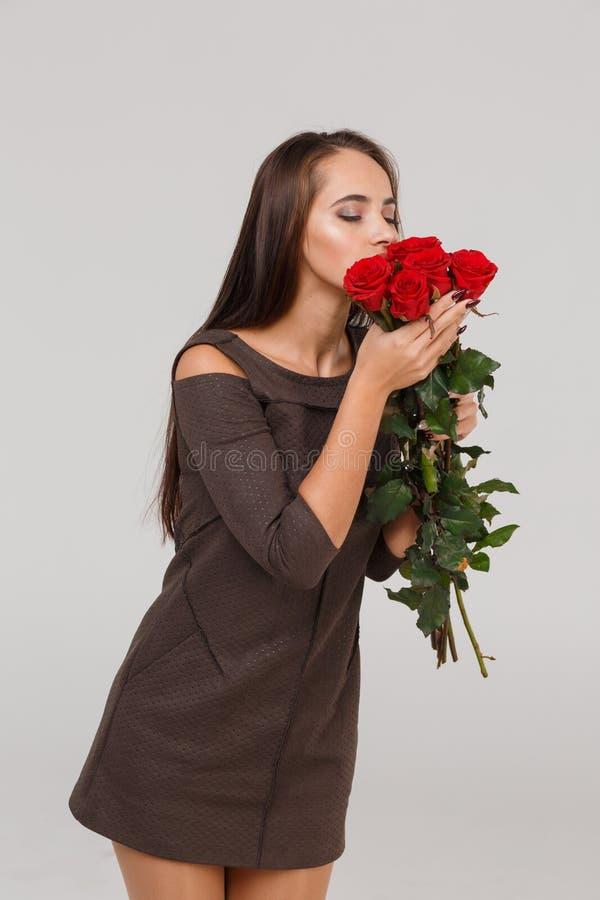 Jeune belle fille avec le bouquet des roses rouges sur un fond gris 8 mars concept images libres de droits
