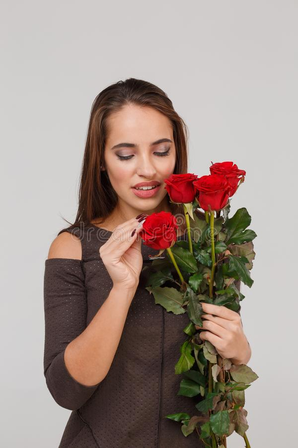 Jeune belle fille avec le bouquet des roses rouges sur un fond gris 8 mars concept images stock