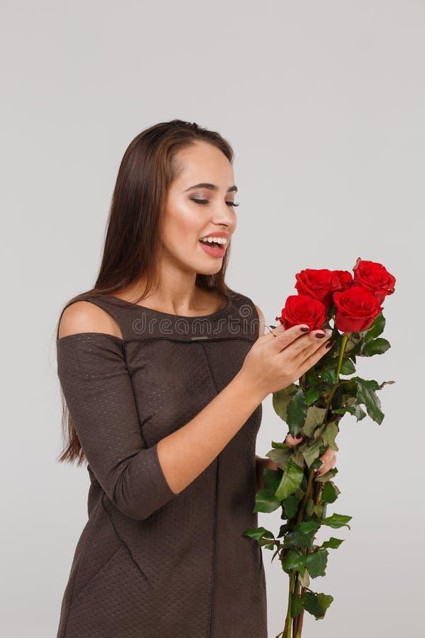 Jeune belle fille avec le bouquet des roses rouges sur un fond gris 8 mars concept photographie stock