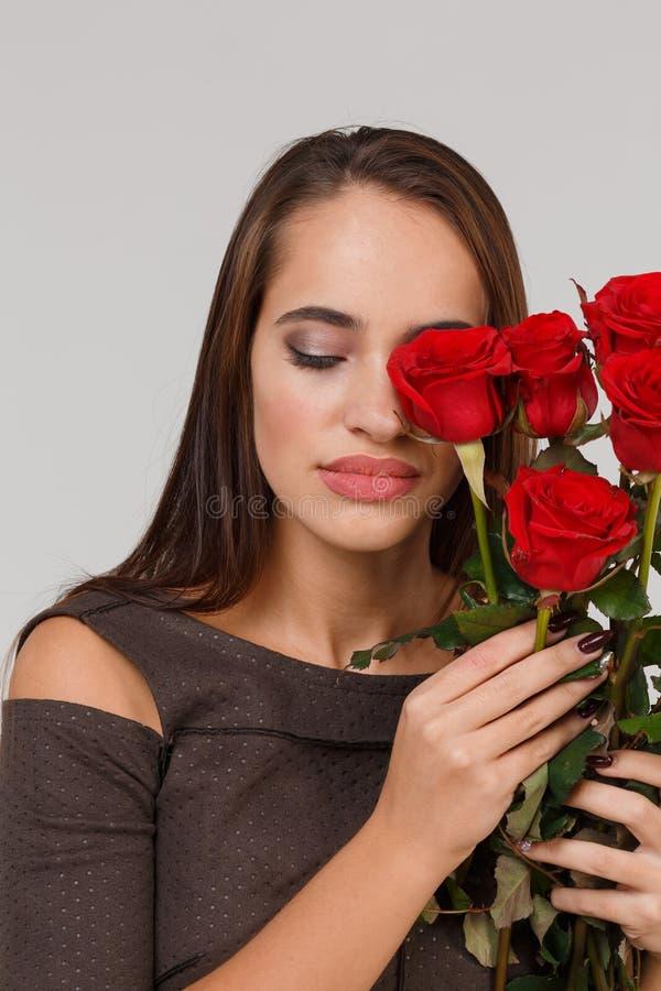 Jeune belle fille avec le bouquet des roses rouges sur un fond gris 8 mars concept photos libres de droits