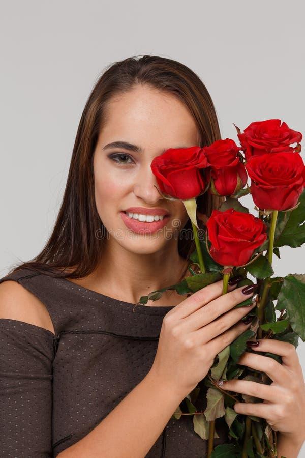 Jeune belle fille avec le bouquet des roses rouges sur un fond gris 8 mars concept image stock