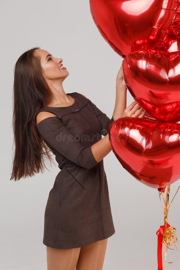 Jeune belle fille avec les ballons à air rouges sur un fond gris 8 mars concept photos libres de droits