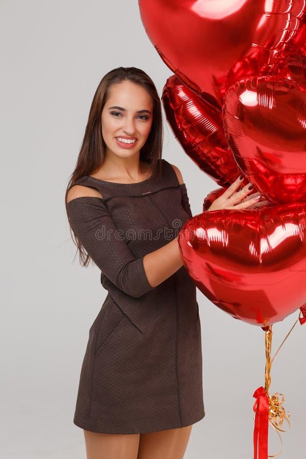 Jeune belle fille avec les ballons à air rouges sur un fond gris 8 mars concept images libres de droits