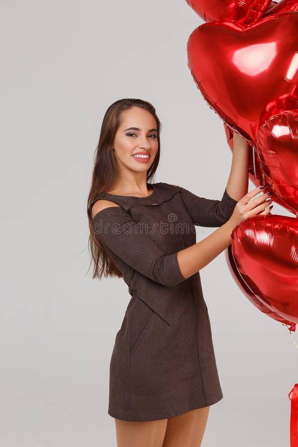 Jeune belle fille avec les ballons à air rouges sur un fond gris 8 mars concept images stock