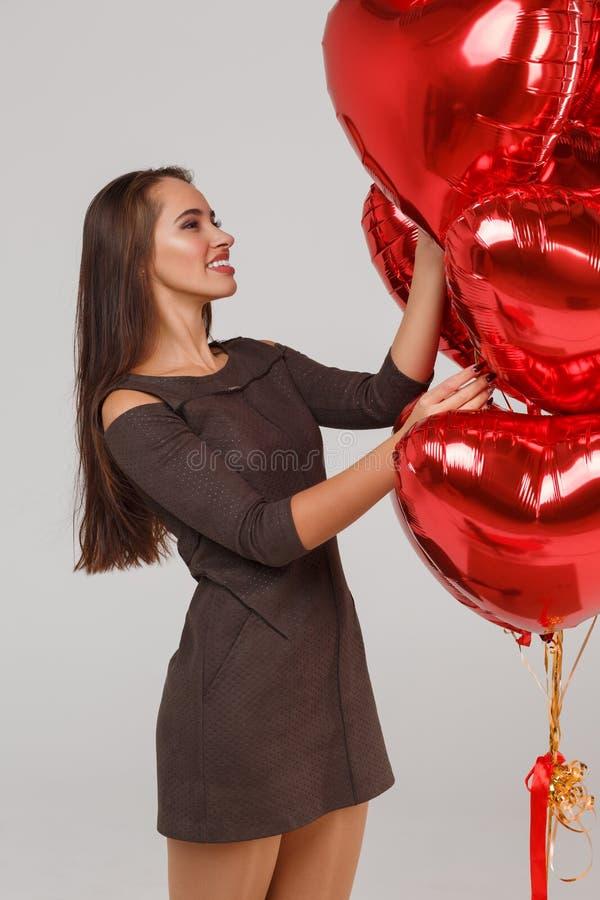 Jeune belle fille avec les ballons à air rouges sur un fond gris 8 mars concept photo libre de droits