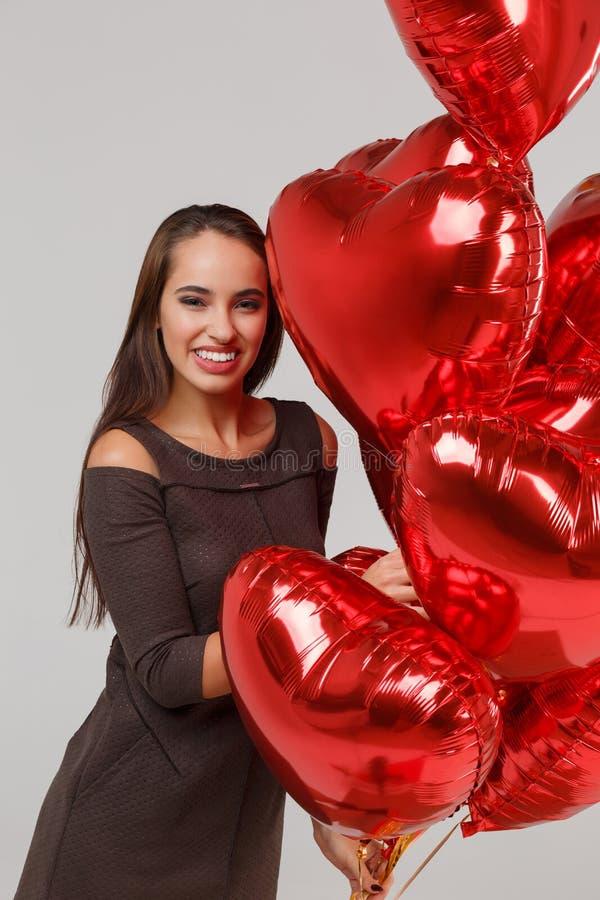 Jeune belle fille avec les ballons à air rouges sur un fond gris 8 mars concept photographie stock