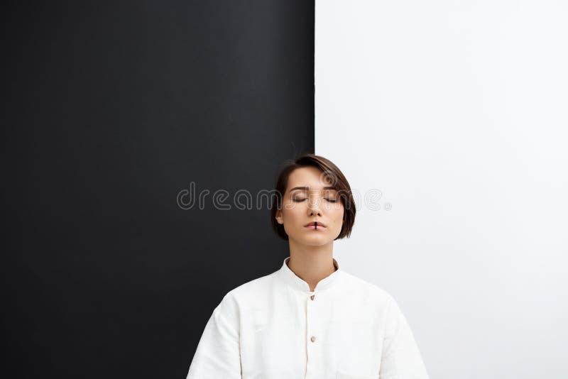 Jeune belle fille avec les yeux fermés au-dessus du fond noir et blanc photos stock