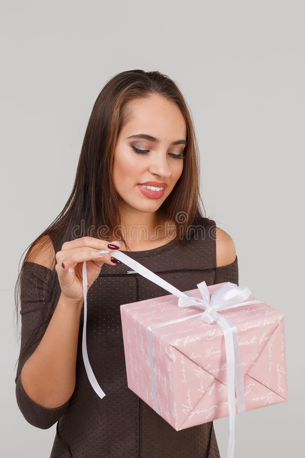 Jeune belle fille avec un cadeau rose sur un fond gris Étonne le concept images libres de droits