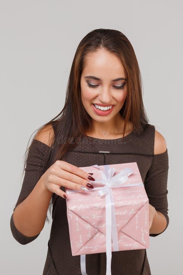 Jeune belle fille avec un cadeau rose sur un fond gris Étonne le concept photos stock