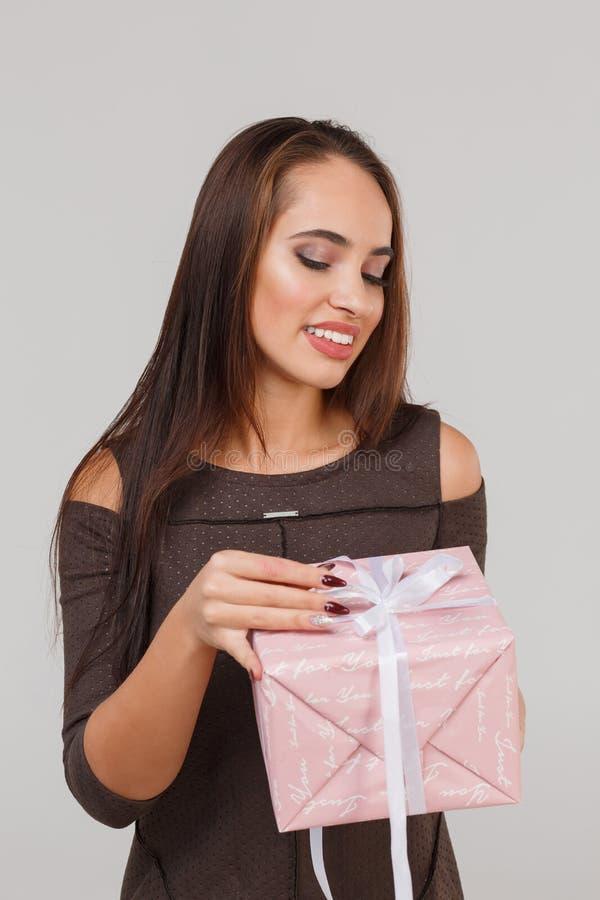 Jeune belle fille avec un cadeau rose sur un fond gris Étonne le concept photo stock