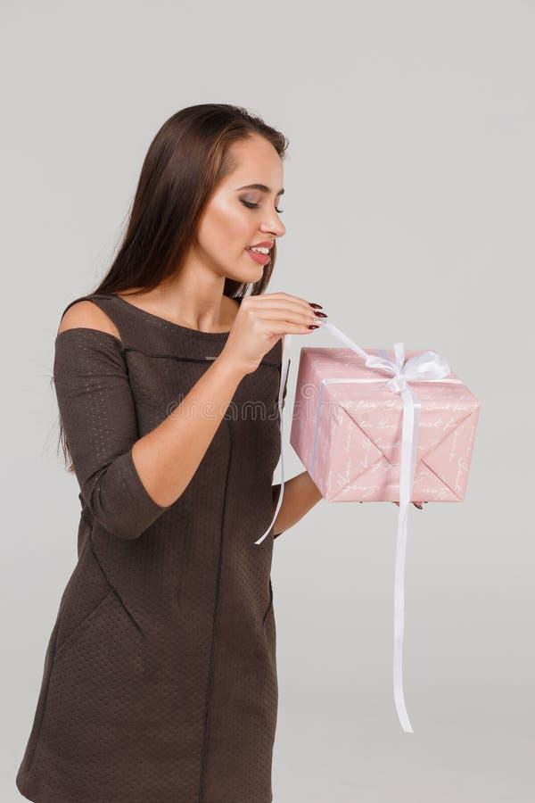 Jeune belle fille avec un cadeau rose sur un fond gris Étonne le concept photographie stock libre de droits