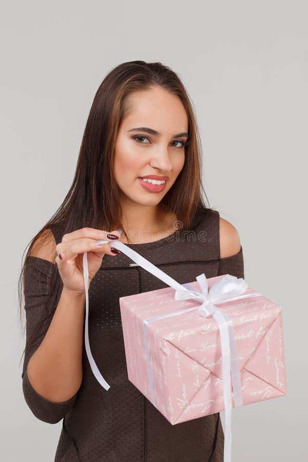 Jeune belle fille avec un cadeau rose sur un fond gris Étonne le concept photographie stock