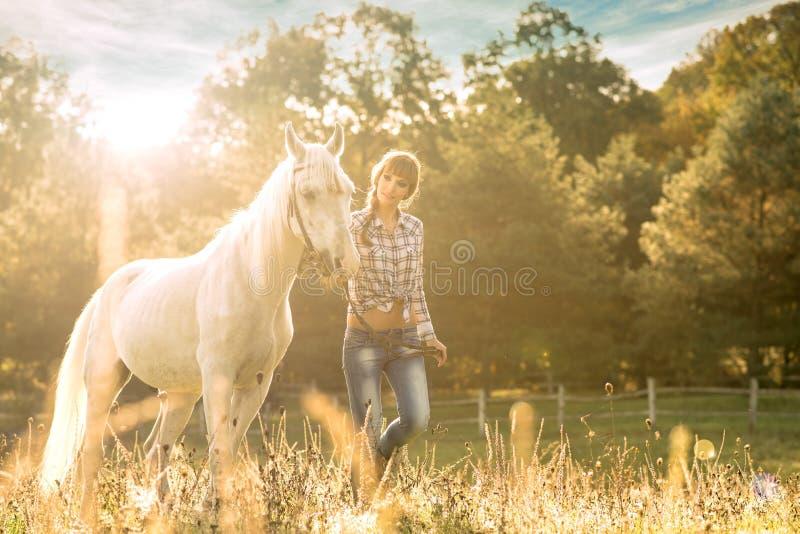 Jeune belle fille avec un cheval sur le champ sec image stock