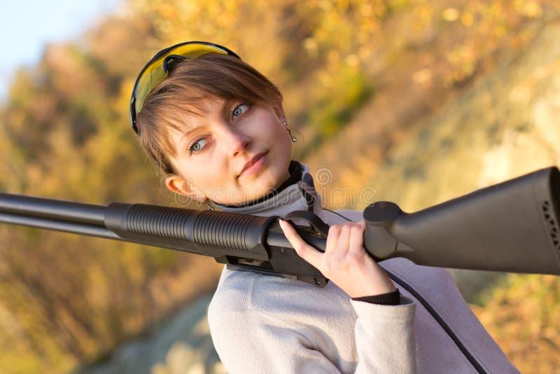 Jeune belle fille avec un fusil de chasse photos stock