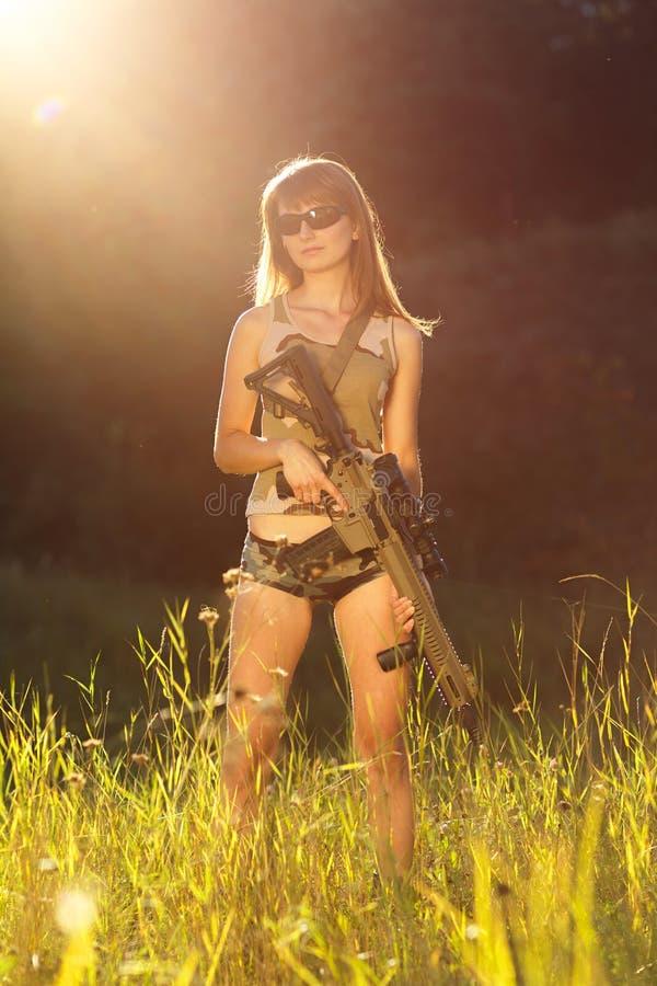 Jeune belle fille avec un fusil de chasse dans un extérieur images stock