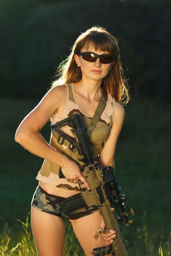 Jeune belle fille avec un fusil de chasse dans un extérieur image libre de droits
