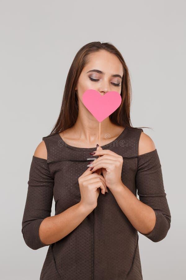 Jeune belle fille avec un peu de coeur rose sur ses lèvres sur un fond gris Concept du ` s de Valentine photo stock