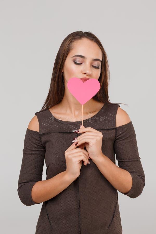 Jeune belle fille avec un peu de coeur rose sur ses lèvres sur un fond gris Concept du ` s de Valentine photos libres de droits