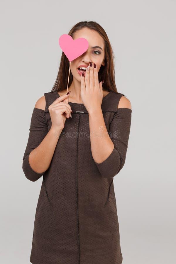Jeune belle fille avec un peu de coeur rose sur ses yeux sur un fond gris Concept du ` s de Valentine photos libres de droits