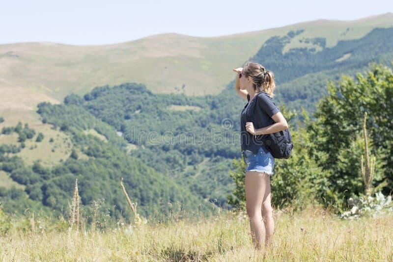 Jeune, belle fille avec un sac à dos sur elle de retour, se tenant sur t photographie stock
