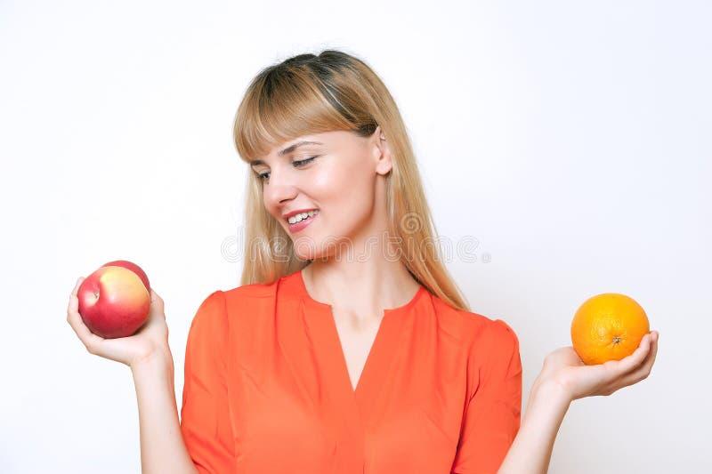 Jeune belle fille blonde choisissant entre la pomme et l'orange. image libre de droits