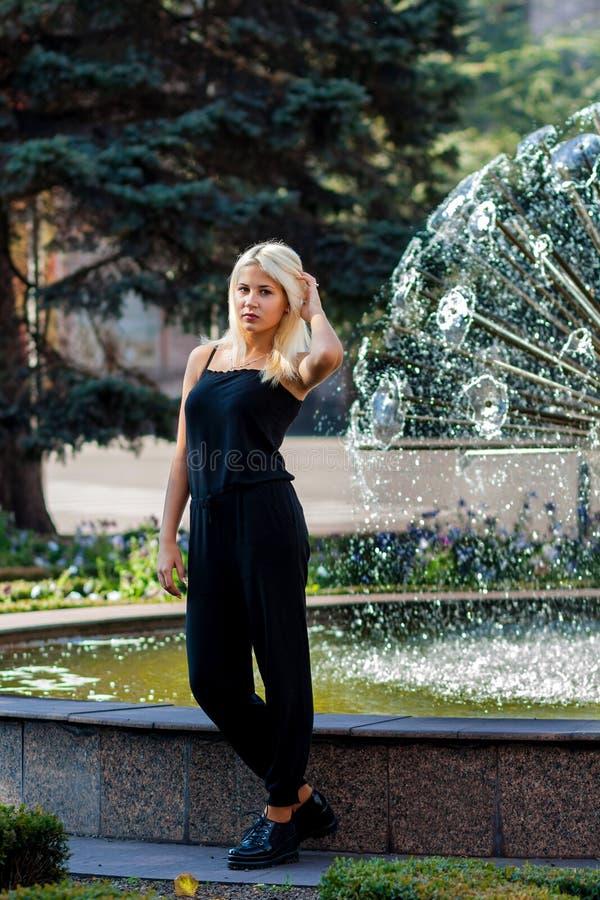 Jeune belle fille blonde posant sur le fond du paysage urbain Dame sexy dans une robe noire photos stock