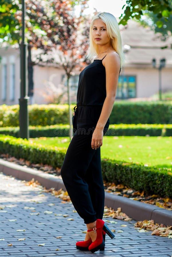 Jeune belle fille blonde posant sur le fond du paysage urbain Dame sexy dans une robe noire et des chaussures rouges images stock