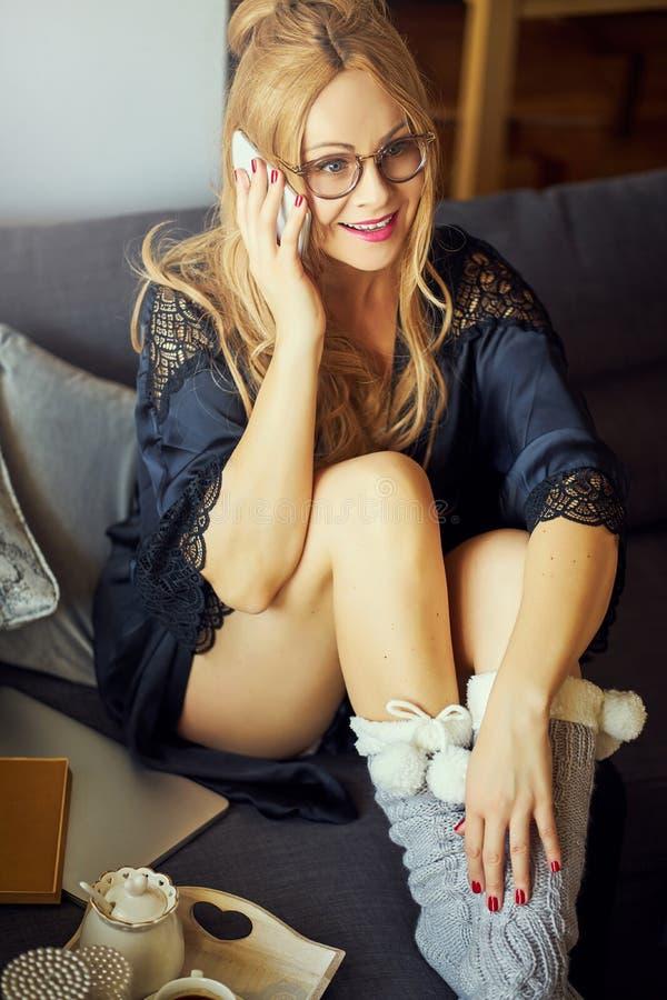Jeune belle fille blonde sur le divan et parler au téléphone images stock