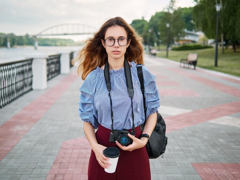 Jeune belle fille d'étudiant en chemisier bleu et verres à la mode ayant l'amusement avec la tasse de l'appareil-photo de café et photos stock