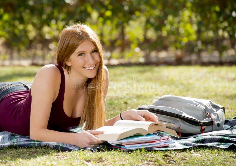 Jeune belle fille d'étudiant sur l'herbe de parc de campus avec des livres étudiant l'examen de préparation heureux dans le conce photos stock